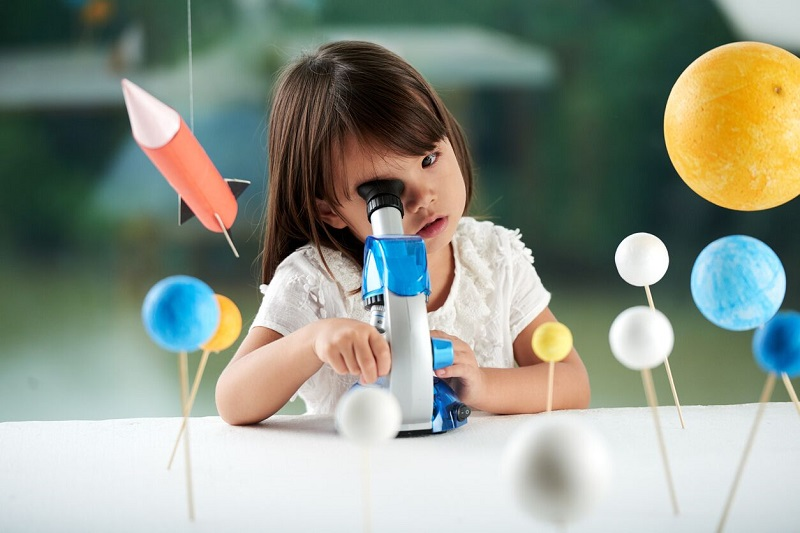 Child studying space science with planets