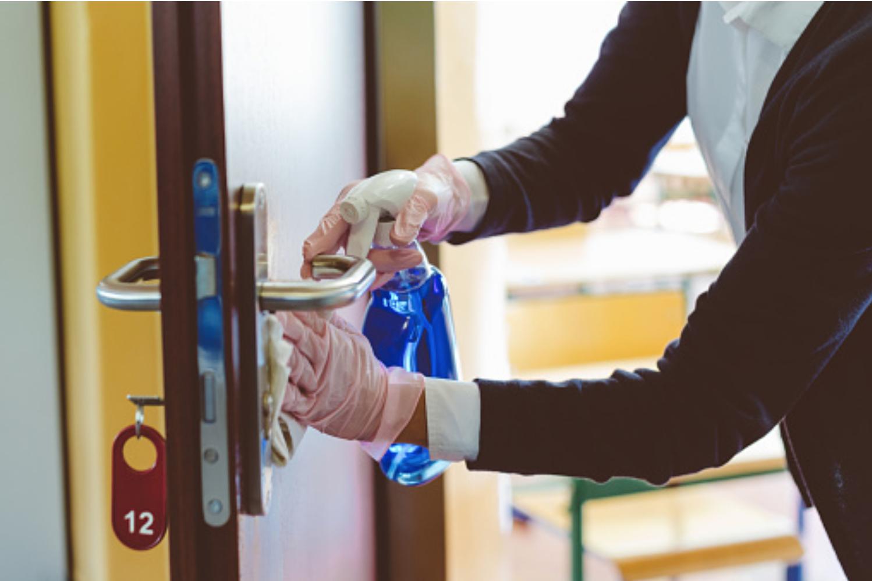 Support staff cleans classroom door handle