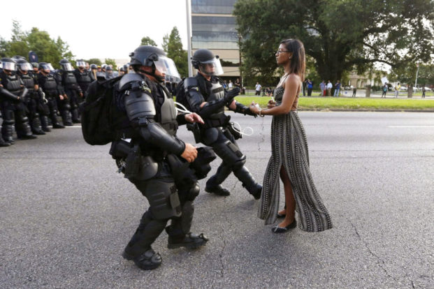 Lone activist Ieshia Evans stands her ground while offering her hands for arrest as she is charged by riot police during a protest against police brutality outside the Baton Rouge Police Department in Louisiana, July 2016