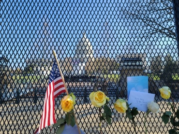 Flowers and notes of encouragement pinned to a fence outside the U.S. Capitol. | Andy Kratochvil