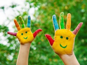 supporting social emotional learning during covid-19 photo of child's hands with painted happy faces
