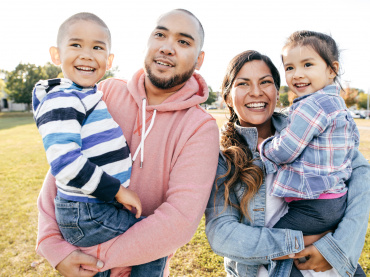 immigrant family smiling at a park