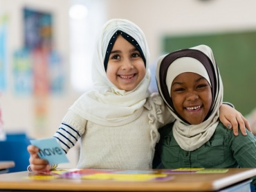 two muslim girls learning together at school