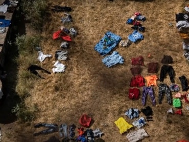 haitian migrants camp at the texas border. seen here are articles of clothing strewn laying on the ground.