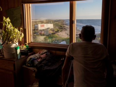 Shelton Kokeok looks through his window at the eroded shoreline. His home is the last one on this part of the island, which is still resisting erosion. Nine years ago, he moved his home 100 feet inland, but the erosion has progressed greatly since then. He doesn't have the resources to move again.
