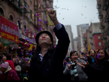 A man reaches for confetti during the Chinese Lunar New Year celebration on January 23, 2012.