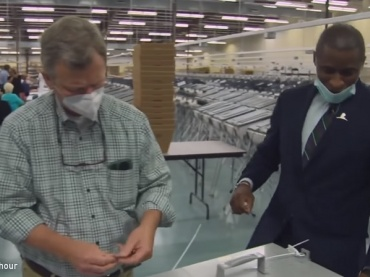 paper and machine voting - two workers unlock ballot boxes