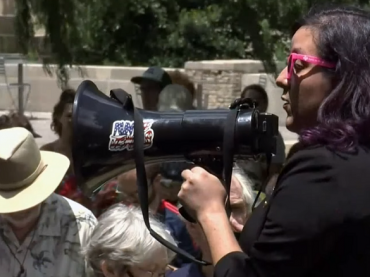 Activist rallying a crowd protesting conditions stemming from today's border crisis