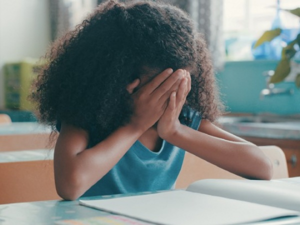 children and grief in school: an upset child is pictured in the classroom