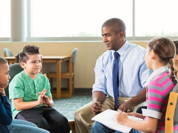 Teacher discussing topics with children in a trauma-informed classroom