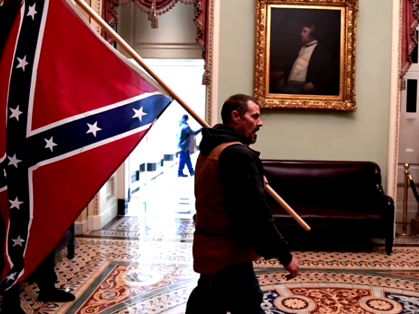 A man holds a confederate flag inside the U.S. Capitol.
