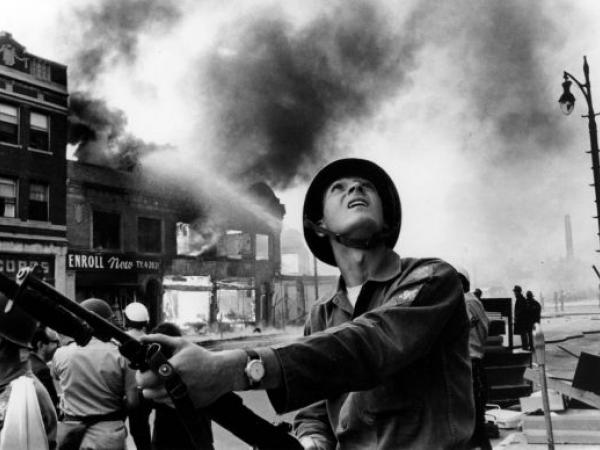 National guardsman Gary Ciko of Hamtramck watches for snipers as buildings burn on Linwood Street, Detroit, Michigan.