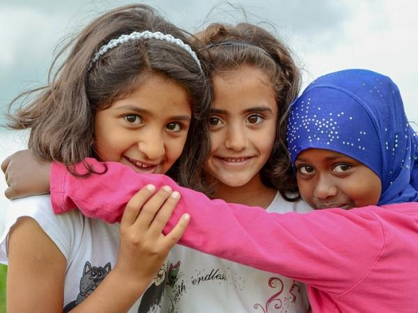 Refugee girls smiling and embracing